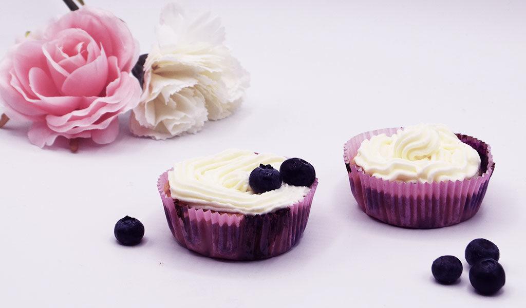 Es sind zwei Blueberry Cheesecake Cupcakes mit Blaubeeren zu sehen