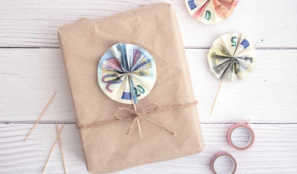 Geschenk mit einer Blume aus gefalteten Geldscheinen als Geldgeschenk