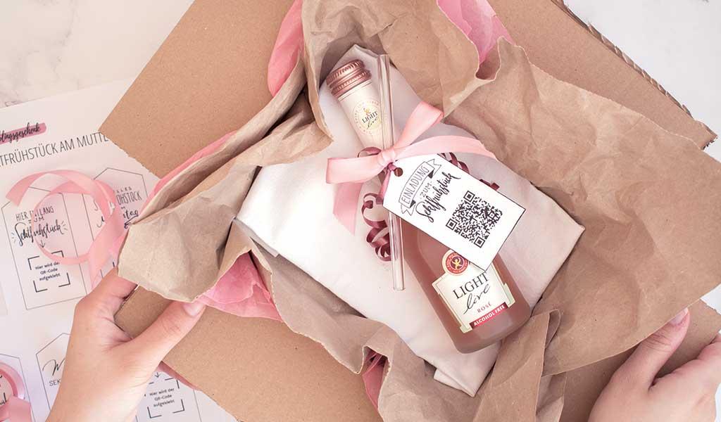 Muttertagsgeschenk: Ein Paket mit der Einladung zum virtuellen Sektfrühstück