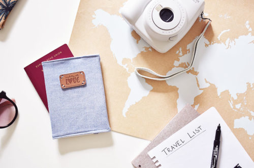 Reisepass aus Jeans zusammen mit weiteren Reiseutensilien