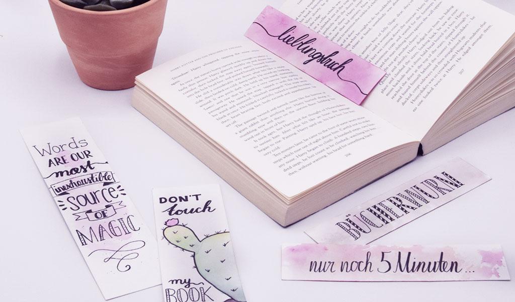 Viele DIY Lesezeichen mit coolen Sprüchen liegen auf dem Tisch mit einem Buch