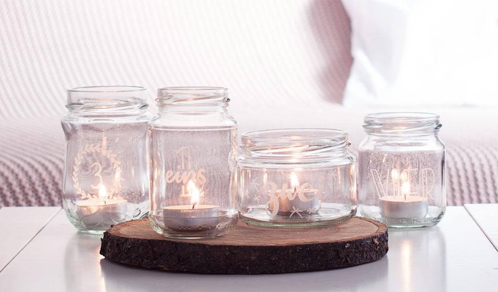 Vier Gläser sind zu einem selbstgemachten Adventskranz verarbeitet